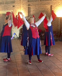 Nancy Butterfly dancers holding up bright red handkerchiefs during a dance at Avoncroft