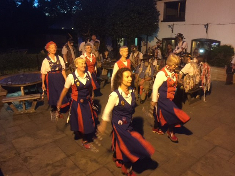 dancing outside the coach and horses inn. It is getting dark but illuminated by lights from the inn.