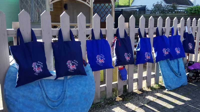 line of bags with nancy butterfly decoration hanging from a picket fence in Upton